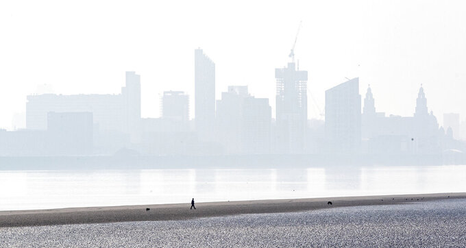 A man walks his dogs along the River Mersey on New Brighton Beach in Liverpool, England, as the UK continues in lockdown to help curb the spread of the coronavirus, Saturday April 11, 2020. The highly contagious COVID-19 coronavirus has impacted on nations around the globe, many imposing self isolation and exercising social distancing when people move from their homes. ( / PA via AP)
