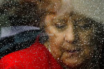 FOR HOLD - FILE - In this Friday, July 12, 2019 file photo, rain drops cover the window of a car as German Chancellor Angela Merkel arrives for the opening of the James-Simon-Galerie of at the Museum's Island in Berlin. Germany prepares for the Sept. 26 election that will determine who succeeds Chancellor Angela Merkel at the helm of Europe's biggest economy, satisfaction with the old government and expectations of the new one vary widely across the country of 83 million. (AP Photo/Markus Schreiber, File)