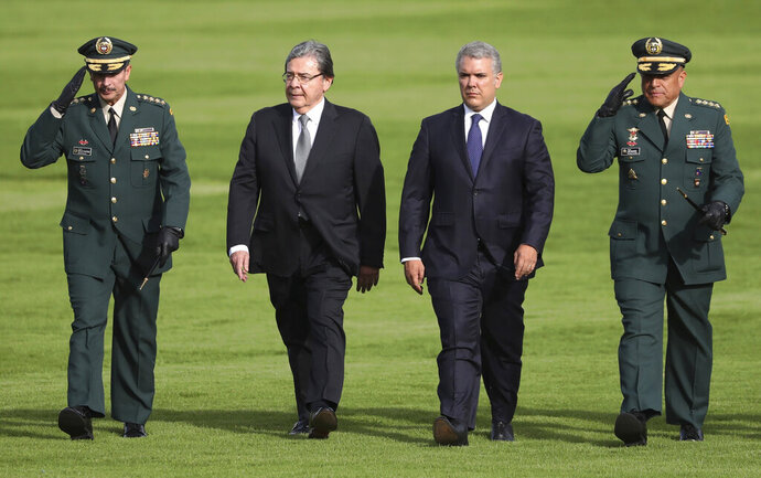 FILE - In this Nov. 16, 2019 file photo, Colombia's army commander, Gen. Nicacio Martinez, from left, new Defense Minister Carlos Holmes Trujillo, President Ivan Duque and Armed Forces Commander Gen. Luis Fernando Navarro, review troops during a military ceremony in Bogota, Colombia. In an article published last Sunday, Semana magazine interviewed members of an elite military intelligence unit who say their superiors ordered them to use software and equipment purchased for spying on terrorist groups, to eavesdrop on high-ranking members of the opposition and on a judge who was overseeing a witness tampering case involving former president Alvaro Uribe. The magazine claims that knowledge of the espionage scandal within some sectors of the government forced the commander of Colombia's army General Nicacio Martinez to resign. (AP Photo/Fernando Vergara, File)