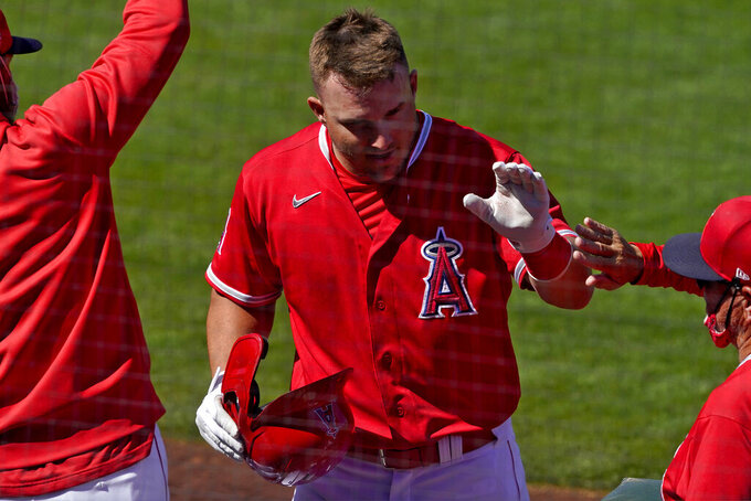 Los Angeles Angels' Mike Trout celebrates after scoring on a double hit by Justin Upton during the second inning of a spring training baseball game against the Chicago Cubs, Monday, March 22, 2021, in Tempe, Ariz. (AP Photo/Matt York)