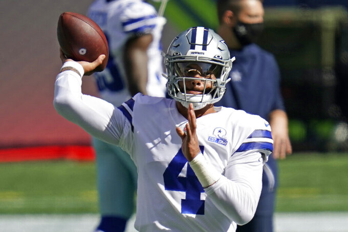 Dallas Cowboys quarterback Dak Prescott passes as he warms up before an NFL football game against the Seattle Seahawks, Sunday, Sept. 27, 2020, in Seattle. (AP Photo/Elaine Thompson)