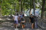 People walk down the stairs in the Montmartre district Monday, Aug. 10, 2020 in Paris. People are required to wear a mask outdoors starting on Monday in the most frequented areas of the French capital. The move comes as the country sees an uptick in virus infections. (AP Photo/Michel Euler)