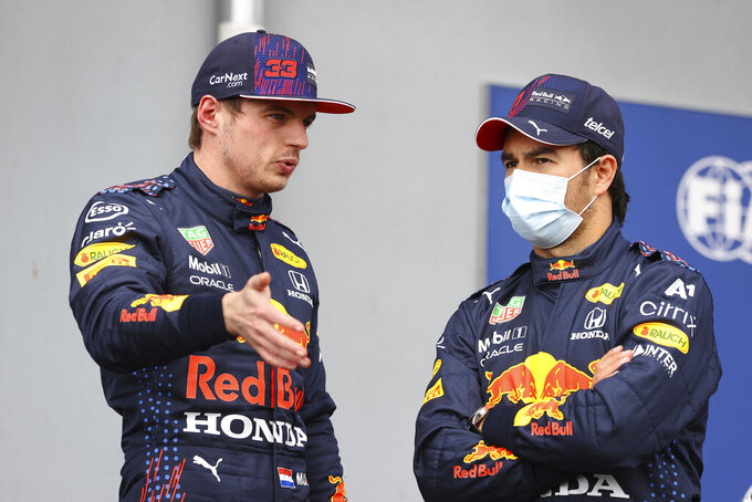 Red Bull driver Max Verstappen of the Netherlands talks with Red Bull driver Sergio Perez of Mexico, right, after qualifying practice for Sunday's Emilia Romagna Formula One Grand Prix, at the Imola track, Italy, Saturday, April 17, 2021. (Bryn Lennon/Pool photo via AP)