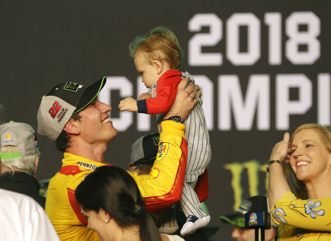 Joey Logano holds his son Hudson after winning the NASCAR Cup Series Championship auto race at the Homestead-Miami Speedway, Sunday, Nov. 18, 2018, in Homestead, Fla. (AP Photo/Lynne Sladky)