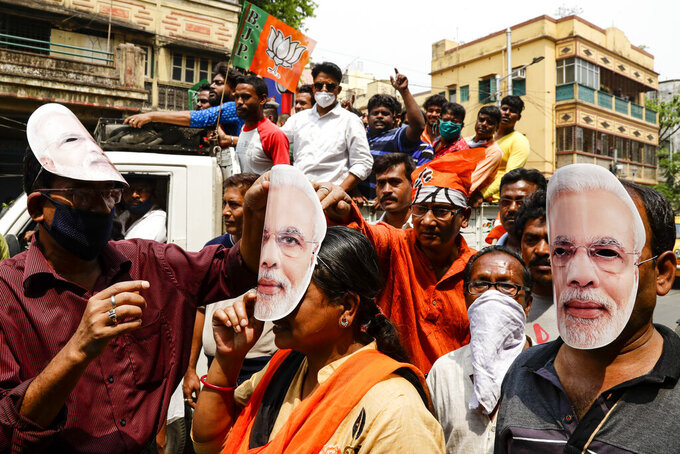 FILE - In this March 20, 2021, file photo, supporters of Bharatiya Janata Party wearing masks bearing the likeness of Prime Minister Narendra Modi participate in a campaign rally ahead of elections in West Bengal state in Kolkata, India. Despite clear signs that India was being swamped by another surge of coronavirus infections, Modi refused to cancel the rallies, a major Hindu festival and cricket matches with spectators. The burgeoning crisis has badly dented Modi's carefully cultivated image as an able technocrat.  (AP Photo/Bikas Das, File)