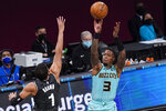 Charlotte Hornets guard Terry Rozier (3) shoots a 3-pointer Brooklyn Nets forward Bruce Brown (1) during the second half of an NBA basketball game Friday, April 16, 2021, in New York. (AP Photo/Mary Altaffer)