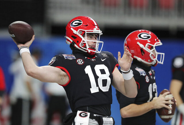 Georgia quarterback JT Daniels (18) and Stetson Bennett prepare to play Cincinnati in the NCAA college football Peach Bowl game on Friday, Jan. 1, 2021, in Atlanta. (Curtis Compton/Atlanta Journal-Constitution via AP)