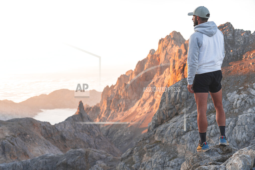 Male tourist looking at mountains while standing on rock, Picos de Europe, Cantabria, Spain