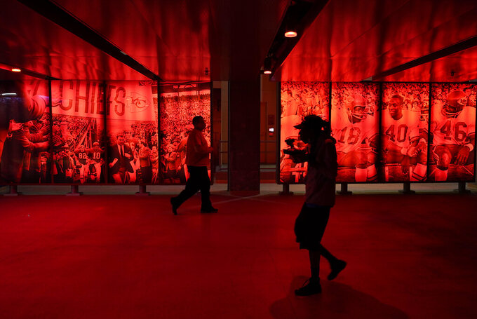 A fan walks through a concourse in Arrowhead Stadium during the first half of an NFL football game between the Kansas City Chiefs and the New England Patriots, Monday, Oct. 5, 2020, in Kansas City. (AP Photo/Charlie Riedel)