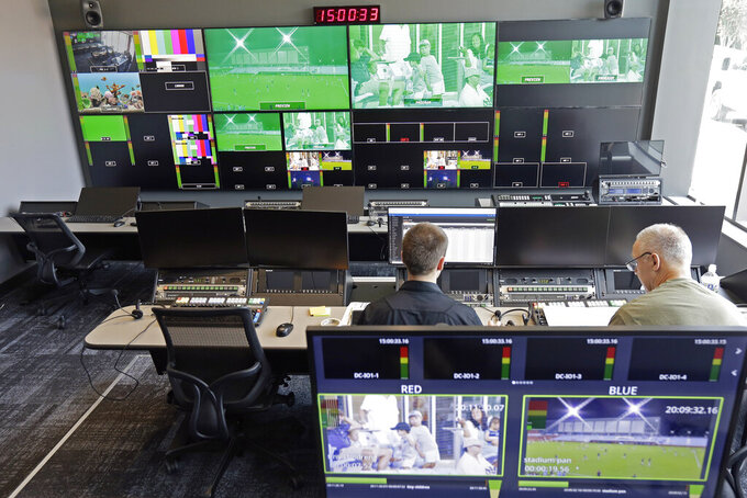 This photo taken Friday, Aug. 23, 2019, shows employees at work in the ACC Network broadcast facility at the University of North Carolina in Chapel Hill, N.C. The Atlantic Coast Conference finally has its TV channel airing hundreds of league sporting events each year thanks in no small measure to its schools. Administrations around the ACC played a critical role in getting the channel up and running, spending millions to ensure campus broadcast and production facilities were capable of handling telecasts. (AP Photo/Gerry Broome)