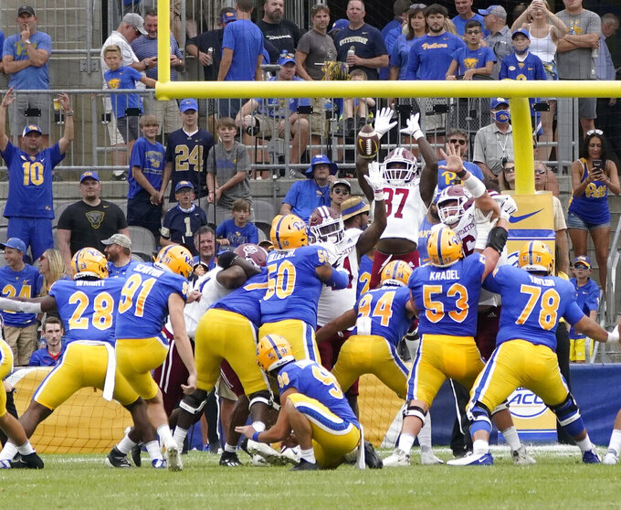 Massachusetts tight end Jacob Orlando (87) leaps trying to block an extra point attempt by Pittsburgh place kicker Sam Scarton (91) during the first half of an NCAA college football game, Saturday, Sept. 4, 2021, in Pittsburgh. The point was good. (AP Photo/Keith Srakocic)