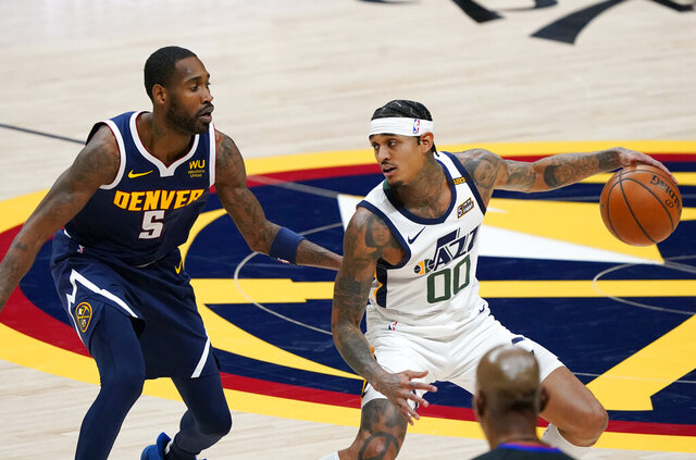 Utah Jazz guard Jordan Clarkson, right, looks to pass the ball as Denver Nuggets forward Will Barton defends in the first half of an NBA basketball game Sunday, Jan. 17, 2021, in Denver. (AP Photo/David Zalubowski)