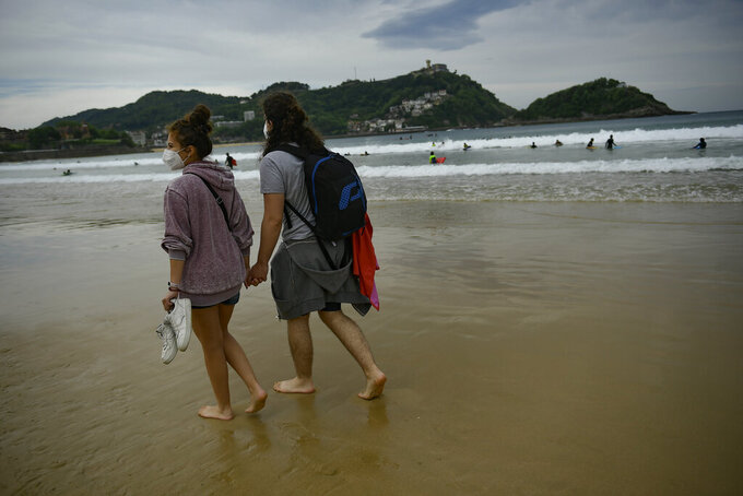 A couple walk along La Concha beach, after lockdown restrictions were lifted, in San Sebastian, northern Spain, Sunday, May 9, 2021. Impromptu street celebrations erupted across Spain as the clock struck midnight on Saturday, when a six-month-long national state of emergency to contain the spread of coronavirus ended and many nighttime curfews were lifted. (AP Photo/Alvaro Barrientos)