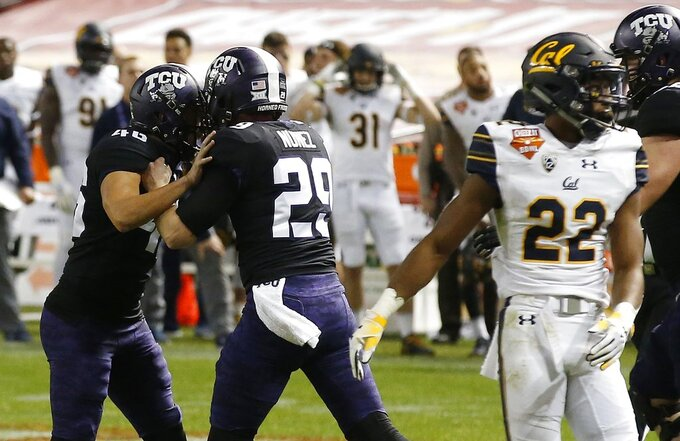 TCU place-kicker Jonathan Song (46) celebrates his game-winning field goal with holder Adam Nunez (29) as California's Traveon Beck (22) looks the other way during overtime of the Cheez-It Bowl NCAA college football game Wednesday, Dec. 26, 2018, in Phoenix. TCU defeated California 10-7. (AP Photo/Ross D. Franklin)