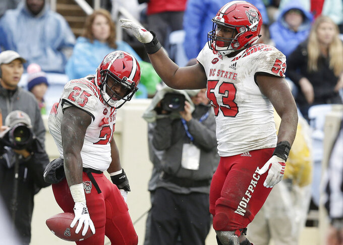 North Carolina State's Reggie Gallaspy II (25) and Tyler Jones (53) celebrate following Gallaspy's touchdown against North Carolina in the second half of an NCAA college football game in Chapel Hill, N.C., Saturday, Nov. 24, 2018. North Carolina State won 34-28 in overtime. (AP Photo/Gerry Broome)