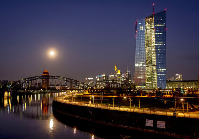 A nearly full moon sets over the buildings of the banking district and the European Central Bank, right, in Frankfurt, Germany, early Tuesday, April 7, 2020. Due to the coronavirus the economy worldwide expects heavy losses. (AP Photo/Michael Probst)