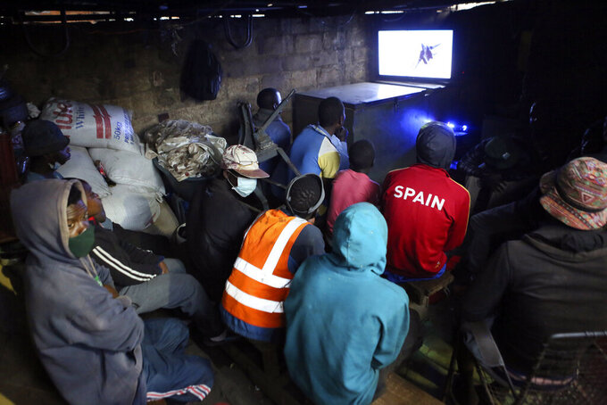 In this photo taken on Tuesday, June, 23, 2020, a group watch a movie at a makeshift home cinema in a neighborhood in Harare. Zimbabweans starved for entertainment, including some children, have turned to petty gambling and other activities in poor neighborhoods where many have lost their livelihoods. Some defy social distancing, crowding shoulder to shoulder. (AP Photo/Tsvangirayi Mukwazhi)