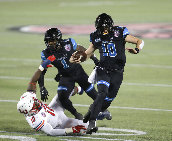 Coastal Carolina quarterback Grayson McCall (10) runs for a first down past Liberty defensive end Tre'Shaun Clark (10) during the second half of the Cure Bowl NCAA college football game Saturday, Dec. 26, 2020, in Orlando, Fla. (AP Photo/Matt Stamey)