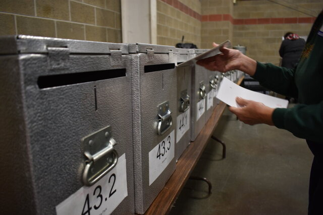 FILE - In this Tuesday, Nov. 6, 2018 file photo an election worker is seen inserting a ballot into a locked ballot box at the Montana Pavilion at MetraPark on election day in Billings, Mont. All 56 of Montana's counties plan to conduct the June 2 primary election by mail due to coronavirus concerns. Ballots will be mailed on May 8. Same-day registration and voting will still be allowed while new laws could mean election results will be available earlier than usual. (AP Photo/Matthew Brow,File)