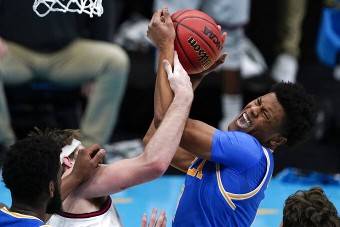 UCLA guard Jaylen Clark, right, fights for a rebound with Gonzaga forward Drew Timme, left, during the first half of a men's Final Four NCAA college basketball tournament semifinal game, Saturday, April 3, 2021, at Lucas Oil Stadium in Indianapolis. (AP Photo/Michael Conroy)