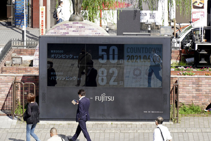 People walk by the countdown clock for the Tokyo 2020 Olympic and Paralympic Games near Shimbashi station in Tokyo, Thursday, June 3, 2021, to mark 50 days before the start of the Summer Games. (AP Photo/Kantaro Komiya)