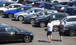 People view cars on the forecourt of a car sales outlet, in Norfolk, England, open for the first time since the lockdown, as part of a wider easing of restrictions in England, Monday June 1, 2020.  The British government has lifted some lockdown restrictions to restart social life and activate the economy while still endeavouring to limit the spread of the highly contagious COVID-19 coronavirus. (Joe Giddens / PA via AP)