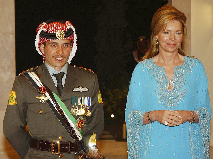 File - In this May 27, 2004, file photo, Jordan's Prince Hamza left, with his mother Queen Noor, right, stand during his wedding ceremony in Amman, Jordan. Prince Hamza, the half-brother of Jordan's King Abdullah II, said he has been placed under house arrest. in a videotaped statement late Saturday, April 3, 2021.(AP Photo/Hussein Malla, File)