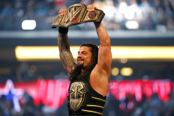 """FILE - In this April 3, 2016, file photo, Roman Reigns holds up the championship belt after defeating Triple H during WrestleMania 32 at AT&T Stadium in Arlington, Texas. WWE is finally making the move to network television. The long-time cable ratings juggernaut is set to begin a billion-dollar deal with Fox with the premier of """"Friday Night Smackdown."""" Dwayne """"The Rock"""" Johnson, Brock Lesnar and Roman Reigns are scheduled to appear for the big debut. (Jae S. Lee/The Dallas Morning News via AP, File)/The Dallas Morning News via AP)"""