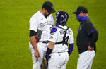 Colorado Rockies relief pitcher Carlos Estevez, left, confers with catcher Tony Wolters and pitching coach Steve Foster after Estevez gave up an RBI double to Los Angeles Dodgers' Corey Seager during the seventh inning of a baseball game Thursday, Sept. 17, 2020, in Denver. (AP Photo/David Zalubowski)