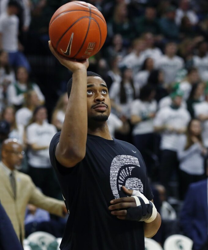 FILE - In this Feb. 20, 2019, file photo, Michigan State forward Nick Ward tosses a basketball before the second half of the team's NCAA college basketball game against Rutgers, in East Lansing, Mich. No. 6 Michigan State expects forward Nick Ward to play in the Big Ten Tournament. Coach Tom Izzo says he isn't sure how much the 6-foot-9 junior will be able to play nearly a month after having surgery on his left hand. The top-seeded Spartans will face the winner of the Ohio State-Indiana game Friday in the conference quarterfinals. (AP Photo/Carlos Osorio, File)