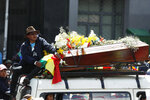 A man sits on top of a van carrying a coffin that contain the remains of a person killed in clashes between supporters of former President Evo Morales and security forces, in a funeral procession into La Paz, Bolivia, Thursday, Nov. 21, 2019. Mourners and anti-government demonstrators marched to La Paz with the coffins of some of the at least eight people killed Tuesday when security forces cleared a blockade of a fuel plant by Morales' backers in the city of El Alto. (AP Photo/Natacha Pisarenko)