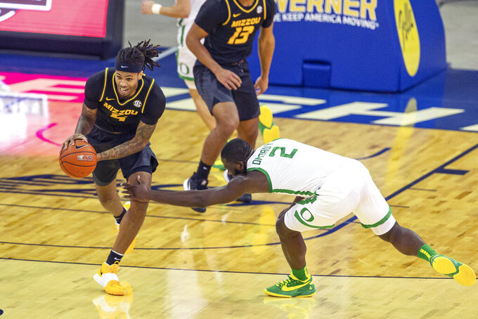 Missouri forward Mitchell Smith (5) steals the ball from Oregon forward Eugene Omoruyi (2) during the first half of an NCAA college basketball game, Wednesday, Dec. 2, 2020 in Omaha, Neb. (AP Photo/John Peterson)