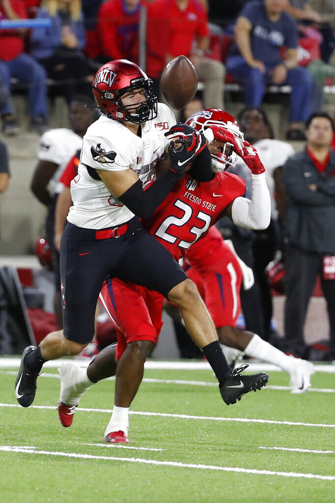 UNLV wide receiver Jacob Gasser, left, tries to haul in a pass that was eventually intercepted, next to Fresno State defensive back Juju Hughes during the first half of an NCAA college football game in Fresno, Calif., Friday, Oct. 18, 2019. (AP Photo/Gary Kazanjian)