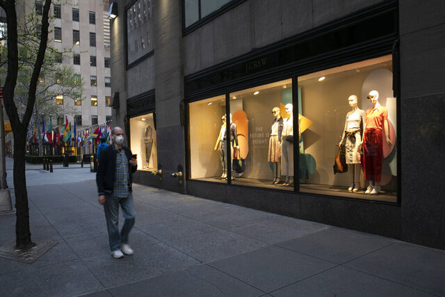 A man wearing a mask walks by a window display at a J Crew store in Rockefeller Center, Saturday, May 2, 2020, in New York. On April 30, the company announced it would apply for bankruptcy protection amidst the COVID-19 pandemic.  (AP Photo/Mark Lennihan)