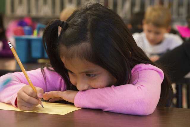 FILE - In this Nov. 26, 2018, file photo, Odalys Tebalan works on an assignment at Fairview Elementary in Carthage, Mo. Millions of children are suddenly learning at home everything from reading and multiplication to literature and calculus as a result of school closures prompted by the global coronavirus pandemic. Many parents are trying to guide their children through assignments, but many face the challenge of English comprehension. (Roger Nomer/The Joplin Globe via AP, File)