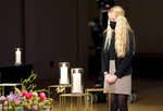 The daughter of a victim of the Corona pandemic attends a memorial service in Berlin, Germany, Sunday, April 18, 2021 in remembrance of Germany's corona dead. (AP Photo/Michael Sohn, pool)