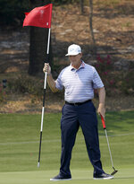 South Africa's Ernie Els plays removes the flag on the first hole during the Australian Open Golf Pro-AM in Sydney, Wednesday, Dec. 4, 2019. The Australian Open begins Thursday. (AP Photo/Rick Rycroft)