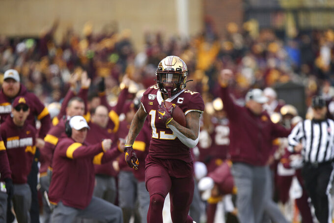 FILE - In this Nov. 9, 2019, file photo, Minnesota wide receiver Rashod Bateman (13) runs the ball down the field for a touchdown against Penn State during an NCAA college football game, in Minneapolis. Bateman has decided to opt back in to the 2020 football season in light of the Big Ten's resumption of fall competition. That's contingent on the star junior gaining the necessary eligibility clearance. (AP Photo/Stacy Bengs, File)