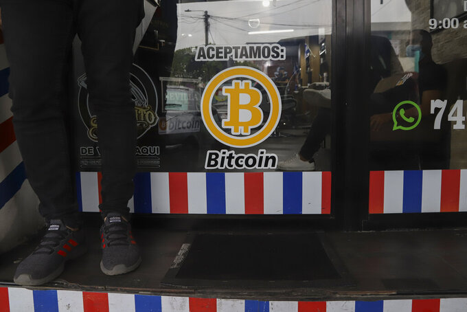 """""""We accept Bitcoin"""" is announced at a barber shop in Santa Tecla, El Salvador, Saturday, Sept. 4, 2021. Starting Tuesday, Sept. 7, all businesses will have to accept payments in Bitcoin, except those lacking the technology to do so. (AP Photo/Salvador Melendez)"""