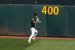 Oakland Athletics center fielder Ramon Laureano catches a ball hit by San Francisco Giants' Brandon Belt for an out during the first inning of a baseball game in Oakland, Calif., Sunday, Sept. 20, 2020. (AP Photo/Jeff Chiu)