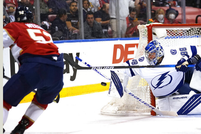 Tampa Bay Lightning goaltender Andrei Vasilevskiy turns away the puck in front of Florida Panthers defenseman MacKenzie Weegar, left, during the second period in Game 2 of an NHL hockey Stanley Cup first-round playoff series Tuesday, May 18, 2021, in Sunrise, Fla. (AP Photo/Lynne Sladky)