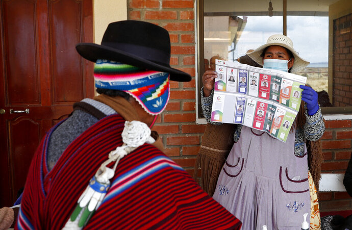 An electoral official shows the ballot to an Aymara man during general elections in Jesus de Machaca, Bolivia, Sunday, Oct. 18, 2020. (AP Photo/Juan Karita)