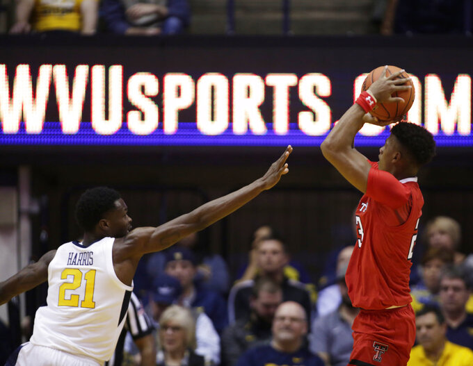 Texas Tech guard Jarrett Culver (23) shoots while defended by West Virginia forward Wesley Harris (21) during the second half of an NCAA college basketball game Wednesday, Jan. 2, 2019, in Morgantown, W.Va. Texas Tech defeated West Virginia 62-59. (AP Photo/Raymond Thompson)