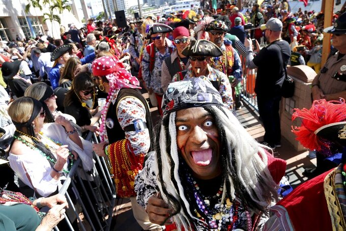 Members of Ye Mystic Krewe of Gasparilla, including Andre Kirwan, of Tampa, foreground, right, arrive at the Tampa Convention Center on the Jose Gasparilla pirate ship during the 103rd Gasparilla Invasion and Parade of the Pirates on Saturday, Jan. 25, 2020, in Tampa, Fla. The parade, which has been held for more than 100 years in Tampa, has been canceled this year due to the coronavirus pandemic. The group says the next one won't be held until January 2022.  (Douglas R. Clifford/Tampa Bay Times via AP)