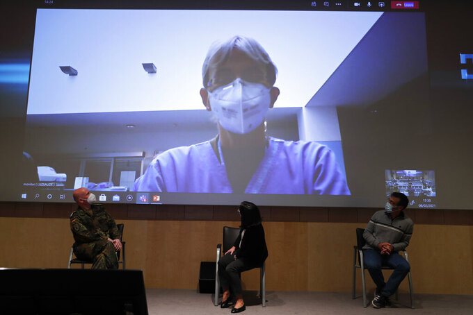 Doctor Jens Peter Evers, left, leader of German military medical team and Doctor Joao Gouveia, right, head of the committee monitoring Portugal's intensive care response to the pandemic, look at a live video image of German doctor Katrin Thinns speaking from inside an ICU manned by German military doctors at the Luz hospital in Lisbon, during a news conference Monday, Feb. 8, 2021. (AP Photo/Armando Franca)