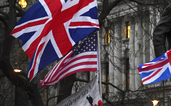 FILE - In this file photo dated Friday, Jan. 31, 2020, Brexit supporters hold British and US flags during a rally in London. The international reputation of the United States has declined further in the wake of its handling of the coronavirus pandemic, according to new research published Tuesday Sept. 15, 2020, from the Pew Research Center. (AP Photo/Alberto Pezzali, FILE)
