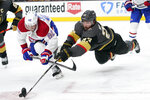 Vegas Golden Knights defenseman Alec Martinez (23) lunges for the puck next to Montreal Canadiens left wing Artturi Lehkonen (62) during the second period in Game 2 of an NHL hockey Stanley Cup semifinal playoff series, Wednesday, June 16, 2021, in Las Vegas. (AP Photo/John Locher)