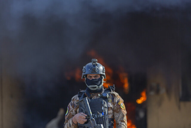 An Iraqi soldier stands guard in front of smoke rising from a fire set by pro-Iranian militiamen and their supporters in the U.S. embassy compound, Baghdad, Iraq, Wednesday, Jan. 1, 2020. U.S. troops fired tear gas on Wednesday as hundreds of Iran-backed militiamen and other protesters gathered outside the American Embassy in Baghdad for a second day and set fire to the roof of a reception area inside the compound. (AP Photo/Nasser Nasser)