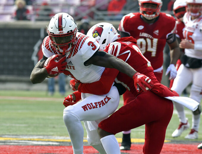 North Carolina State wide receiver Kelvin Harmon (3) fights to get out of the grasp of Louisville cornerback Anthony Johnson (27) during the first half of an NCAA college football game, in Louisville, Ky., Saturday, Nov. 17, 2018. (AP Photo/Timothy D. Easley)