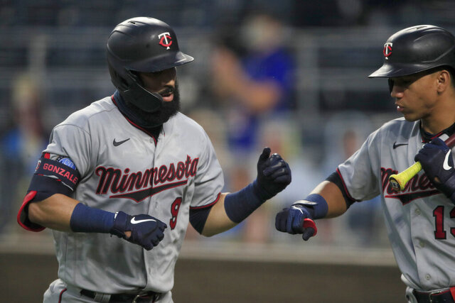 Minnesota Twins' Marwin Gonzalez (9) is congratulated by teammate Ehire Adrianza (13) after his solo home run during the fourth inning of a baseball game against the Kansas City Royals at Kauffman Stadium in Kansas City, Mo., Friday, Aug. 7, 2020. (AP Photo/Orlin Wagner)